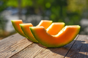 Slices of melon on a wooden background