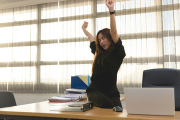 Asian officer woman stretching body at the desk of office