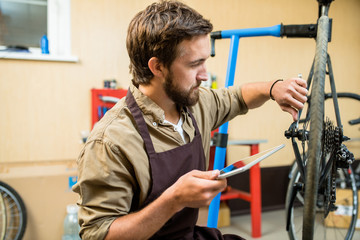 Repair specialist with tablet searching in the net about fixing wheel of bike