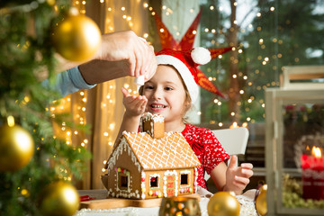 Adorable little girl in red hat decorating gingerbread house with glaze. Beautiful living room with lights and Christmas tree, table with candles and lanterns. Cute child celebrating holiday.