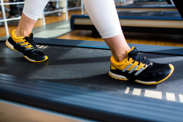 Human feet on threadmill moving track during workout in gym