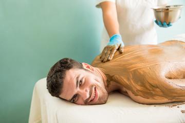 Hispanic young man during a mud bath