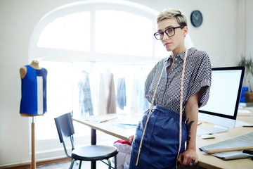 Young creative fashion-designer looking at camera by her workplace in studio