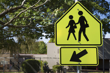 Bright Yellow and Black Pedestrian Crosswalk Sign with Figure of Man and Woman, Out of Focus Building/People in Background
