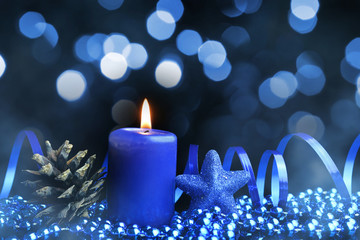 Blue Christmas decorations with pine cone and burning candle. Holiday background.