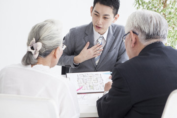The real estate salesperson is presenting to the elderly couple