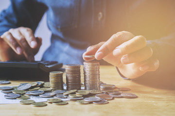concept saving money with hand putting coins stack for finance and accounting