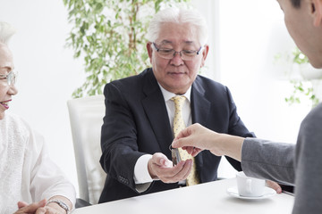 A salesperson gives an old man the key of the property
