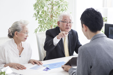 An old couple talking to sales representatives