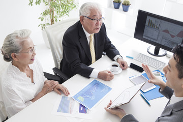 Sales person and old couple are simulating mortgage