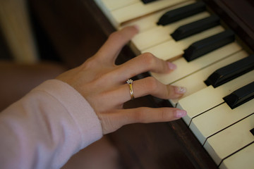 Focus One Female Hand Playing Wood Piano with her Ring