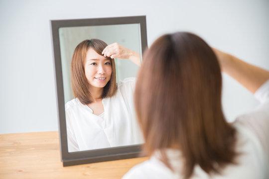前髪を気にする女性(笑顔)