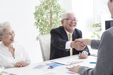 An old man shaking hands with a salesperson