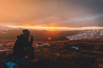 Hiker with backpack sitting on top of a mountain and enjoying sunrise