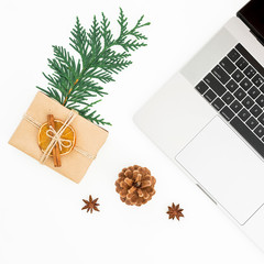 New year composition with laptop, Christmas gift box and pine cone on white background. Top view. Flat lay