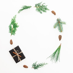 Christmas frame made of gift box, branches and pine cones on white background. New year composition. Flat lay. Top view