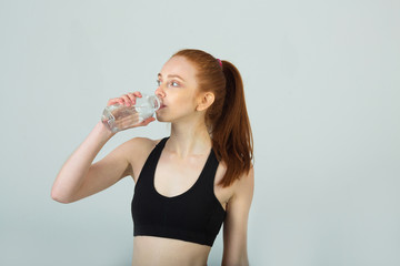 beautiful slender girl with red hair in sportswear on a light background with a bottle of water