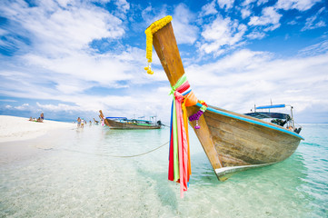 Traditional Thai wooden longtail boat with decorative sash ribbons moored in crystal waters on the shore of Bamboo Island near Krabi