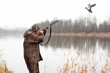 Acrylic Prints Hunting hunter shooting to the flying duck
