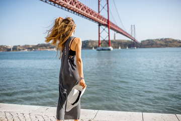 Woman enjoying beautiful landscape view on the famous iron bridge standing back near the river in Lisbon, Portugal