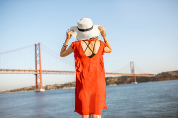 Woman in red dress enjoying landscape view on the famous iron bridge standing back on the riverside in Lisbon city, Portugal