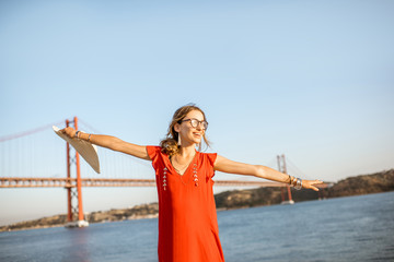 Woman having fun standing on the riverside with beautiful view on the iron bridge traveling in Lisbon city, Portugal