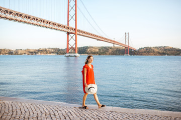 Lifestyle portrait of a woman in red dress walking on the riverside with beautiful iron bridge on the background in Lisbon city, Porugal