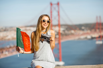 Portrait of a young and cute woman with photo camera and portuguese flag on the landscape view background with beautiful iron bridge traveling in Lisbon city, Portugal