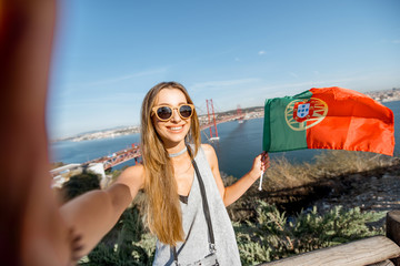 Young woman making selfie photo with portuguese flag on the beautiful landscape view background with bridge and river in Lisbon, Portugal