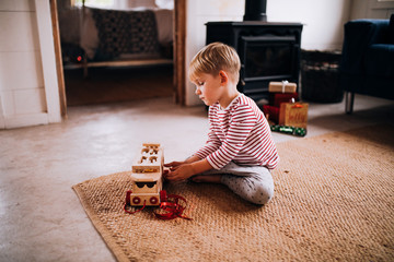 Boy plays with new wooden toy truck