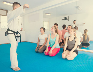 Young instructor is showing new martial moves to adults