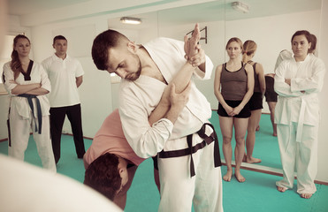 Coach explaining painful hold in taekwondo class