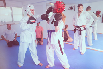 Females are sparring in pair to use taekwondo technique