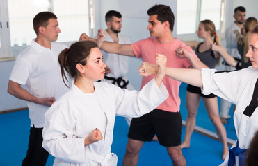 Adult men and women are practicing new karate moves in pairs
