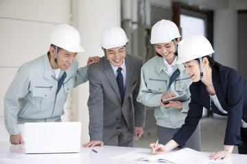 建設現場で打ち合わせをする男女4人