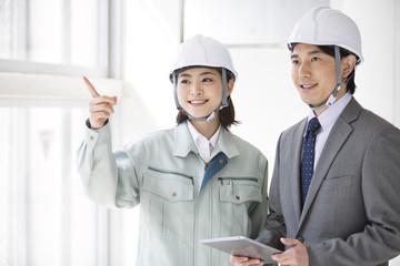 建設現場で打ち合わせをする男女2人