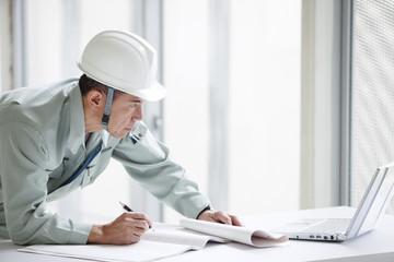 建設現場で図面を見る男性作業員