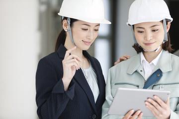 建設現場でタブレットPCを見る女性2人