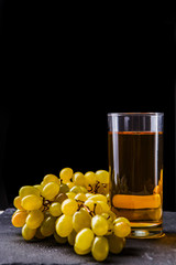 Picture of glass with juice, bunch of grapes on stone board