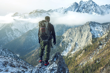 Obraz Man hiker with backpack on top of the mountain back, looking at the snow slope. Concept motivation and goal achievement - fototapety do salonu