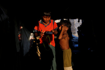The Wider Image: Rohingya refugee boy works to support family