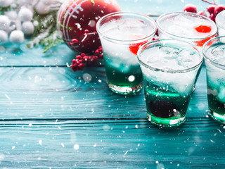 Christmas holiday party background with green alcohol drinks with cherry. Festive aperitif shots and ornaments on wooden dark table