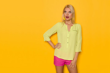 Surprised Beautiful Blond Woman In Yellow Shirt And Pink Shorts Is Looking Away