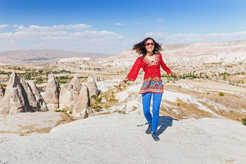 Young happy woman travels alone on beautiful Cappadocia and enjoying great view, Turkey