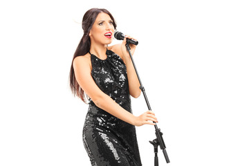 Female singer in a black dress singing on a microphone