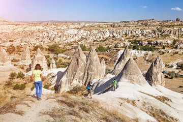 Group of happy caucasian Friends travelling among Cappadocia fairy chimneys at summer