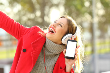 Happy woman listening to music and showing phone