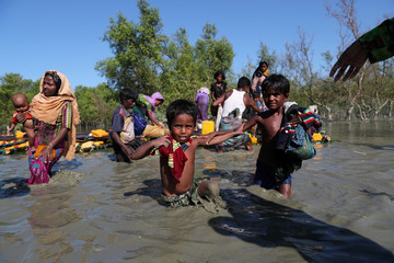 Rohingya refugees come out of an improvised raft after crossing the Naf River at Sabrang near Teknaf