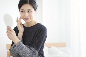 手鏡を見る中高年女性
