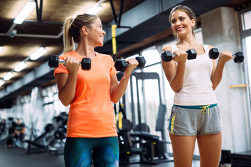 Young women doing exercises in gym together